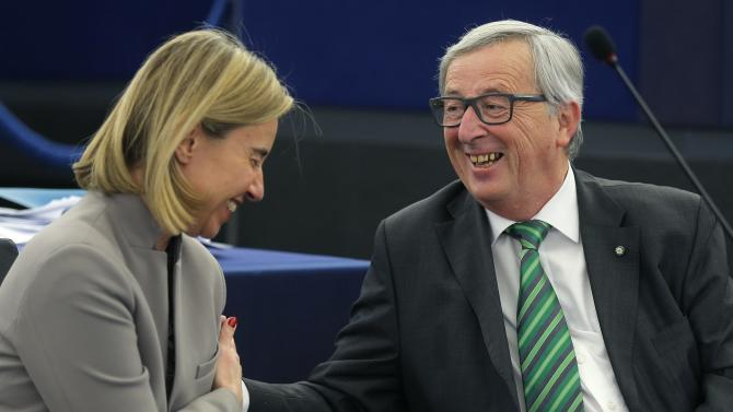 European Commission President Juncker jokes with European Union Foreign Policy Chief Mogherini during a debate at the European Parliament in Strasbourg