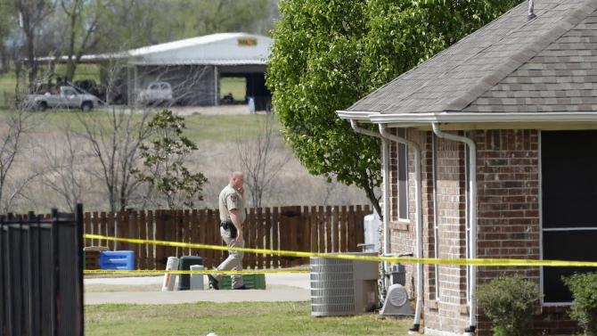 A Kaufman County Sheriff's deputy walks near the taped-off property of Kaufman County District Attorney Mike McLelland, near Forney, Texas, on Sunday, March 31, 2013. On Saturday, McLelland and his wife, Cynthia, were murdered in their home. (AP Photo/Mike Fuentes)