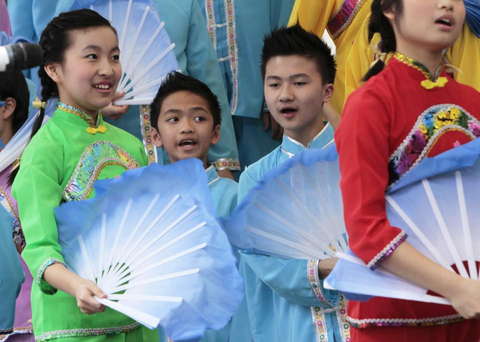 In this Thursday, July 12, 2012 photo, members of the Hong Kong Yuen Long Children's Choir, from Hong Kong, use fans during a performance, on Fountain Square in Cincinnati. Hundreds of choirs from around the world are competing in 23 categories in the event that ends Saturday. (AP Photo/Al Behrman)