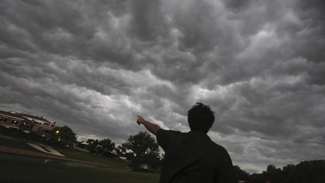 John Bauman point out an looming storm over the Colonial Country Club as golf fans leave the venue hosting the second round of the Colonial golf tournament, Friday, May 24, 2013, in Fort Worth, Texas. Play was suspended due to the weather. (AP Photo/LM Otero)