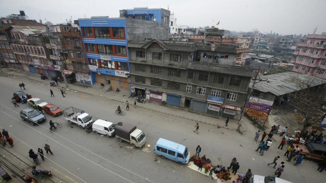 Nepalese rest on a  road beside a line of parked vehicles, a day after a massive earthquake devastated the region and destroyed homes and infrastructure, in Kathmandu, Nepal, Sunday, April 26, 2015. Sleeping in the streets and shell-shocked, Nepalese cremated the dead and dug through rubble for the missing Sunday even as the worst of the aftershocks, magnitude 6.7, pummeled the capital city. (AP Photo/Bikram Rai)