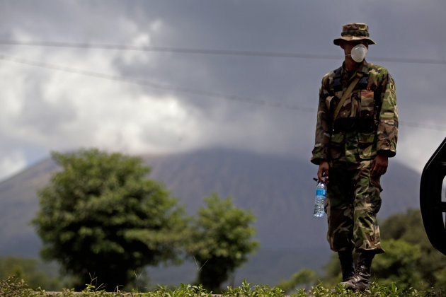 A Nicaraguan soldier wears a protective mask as the San Cristobal volcano, in background, spews smoke and ash, near Chinandega, Nicaragua, Saturday, Sept. 8, 2012. Nicaragua's tallest volcano, located