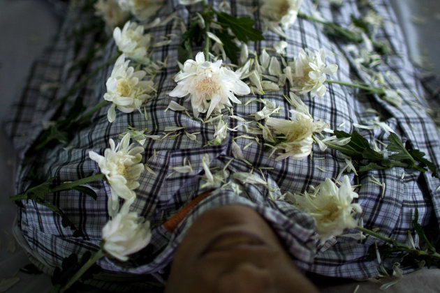 In this Sept. 4, 2012 photo, white chrysanthemum flowers are arranged on the body of HIV victim Kyaw Naing Aung, who died a day earlier at the age of 29, during his funeral on the outskirts of Yangon, Myanmar. Myanmar ranks among the world&#39;s hardest places to get HIV care, and health experts warn it will take years to prop up a broken health system hobbled by decades of neglect. (AP Photo/Alexander F. Yuan)