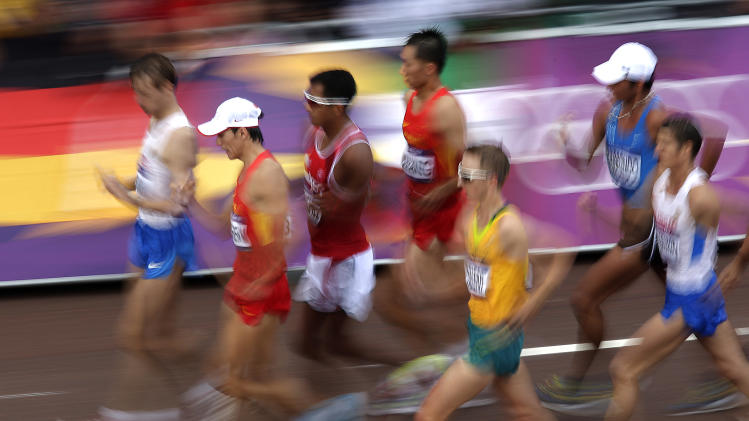 Athletes compete in the men's 20-kilometer race walk near Buckingham Palace during the 2012 Summer Olympics  Saturday, Aug. 4, 2012, in London. (AP Photo/Charlie Riedel)