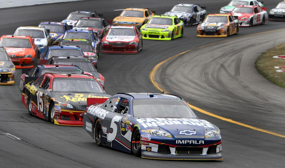 Kasey Kahne (5) takes the lead over Clint Bowyer during a restart at the NASCAR Sprint Cup Series auto race, Sunday, July 15, 2012, at New Hampshire Motor Speedway in Loudon, N.H. Kahne won the race. (AP Photo/Jim Cole)