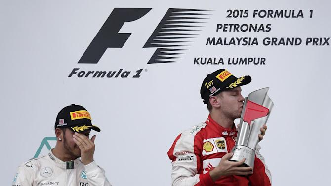 Ferrari driver Sebastian Vettel of Germany kisses his trophy next to Mercedes driver Lewis Hamilton of Britain on the podium after winning the Malaysian Formula One Grand Prix at Sepang International Circuit in Sepang, Malaysia, Sunday, March 29, 2015. Hamilton finished second. (AP Photo/Andy Wong)