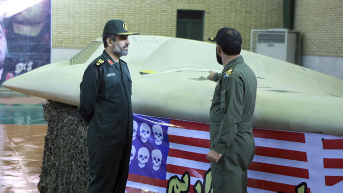 FILE - This photo released on Thursday, Dec. 8, 2011 by the Iranian Revolutionary Guards, claims to show the chief of the aerospace division of Iran's Revolutionary Guards, Gen. Amir Ali Hajizadeh, left, listening to an unidentified colonel pointing to a U.S. RQ-170 Sentinel drone which Tehran says its forces downed. Hajizadeh warned that Iran will target U.S. bases in the region in the event of war with Israel, raising the prospect of a broader conflict that would force other countries to get involved, Iranian state television reported Sunday, Sept. 23, 2012. (AP Photo/Sepahnews, File) THE ASSOCIATED PRESS HAS NO WAY OF INDEPENDENTLY VERIFYING THE CONTENT, LOCATION OR DATE OF THIS IMAGE