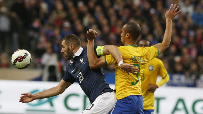 France's captain Karim Benzema, left, and Brazil's Miranda challenge for the ball during the friendly soccer match between France and Brazil at the Stade de France, north of Paris, France, Thursday, March 26, 2015. Brazil won against France 3-1. (AP Photo/Michel Euler)
