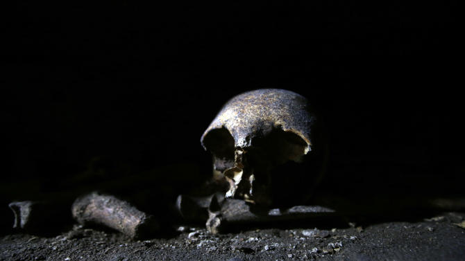 A skull lies in a niche in the Catacombs of Priscilla, a labyrinthine cemetery complex that stretches for kilometers underground, in Rome, Tuesday, Nov. 19, 2013. The Vatican has unveiled newly restored frescoes in the Catacombs of Priscilla, known for housing the earliest known image of the Madonna with Child, and frescoes said by some to show women priests in the early church. The catacombs feature a tiny, delicate Madonna fresco dating from 230-240 AD, as well as scenes said by proponents of the women's ordination movement to show women priests. (AP Photo/Gregorio Borgia)