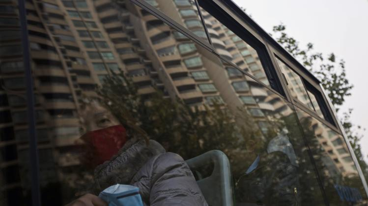 A woman wears a mask while holding another as she sits on a public bus during a hazy day in downtown Shanghai