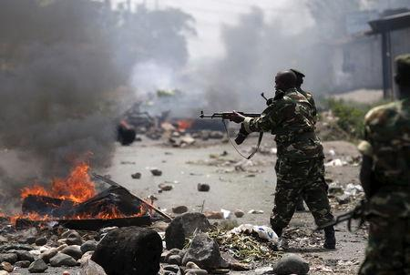 A soldier fires an AK-47 rifle during a protest against President Pierre Nkurunziza and his bid for a third term, in Bujumbura