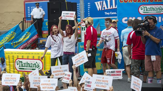 Animal rights activists storm the podium following the annual Fourth of July 2015 Nathan's Famous Hot Dog Eating Contest in Brooklyn, New York