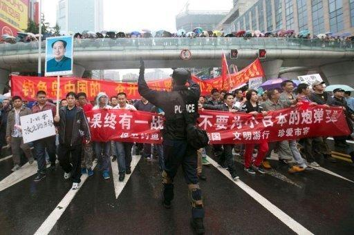 A Chinese riot policeman directs protesters in Chengdu, Sichuan province