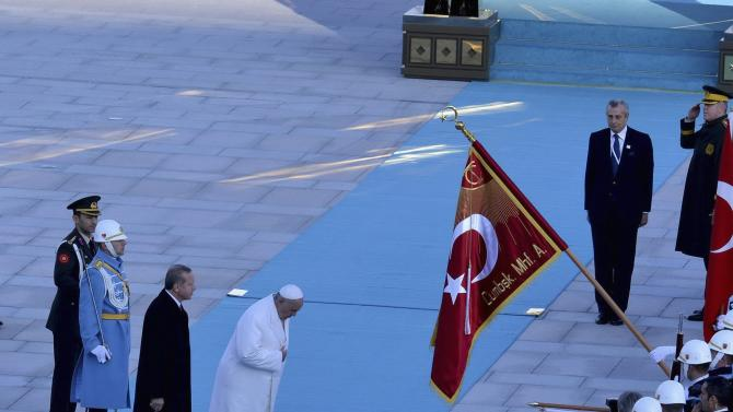 Pope Francis, accompanied by Turkey's President Erdogan, reviews a guard of honour during a welcoming ceremony at the Presidential Palace in Ankara