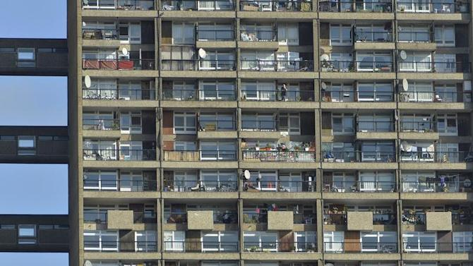 A man stands on a balcony in a residential high rise block of flats in North Kensington in central London