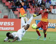 Ghana's midfielder Christian Atsu (R) vies with Niger's defender Kourouma Fatokouma (down) during the 2013 Africa Cup of Nations football match Niger vs Ghana at Nelson Mandela Bay Stadium in Port Elizabeth on January 28, 2013. Ghana won 3-0.