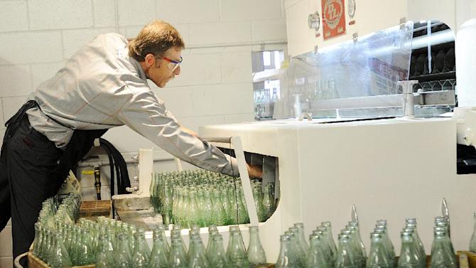 FILE - In this Tuesday, Oct. 9, 2012, photo, Darvin Peterson loads glass bottles into a washer before they are filled up for the last time at the Coca-Cola Bottling Company in Winona, Minn. Nearly 6,000 6.5-ounce returnable glass bottles were filled for the last time after 80 years of production. (AP Photo/Winona Daily News, Andrew Link)