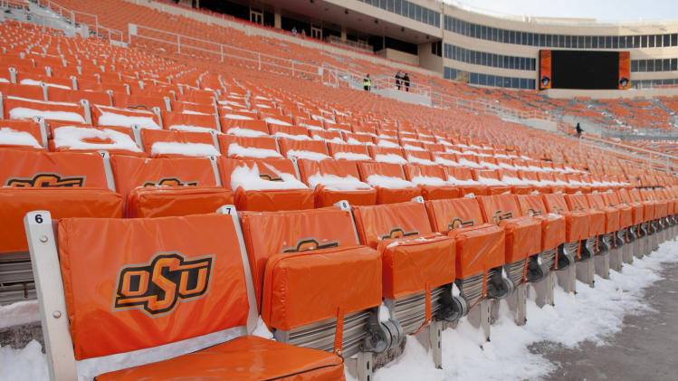 Snow covered seats await fans prior the start of the Oklahoma-Oklahoma State NCAA college football game in Stillwater, Okla., Saturday, Dec. 7, 2013. (AP Photo/Brody Schmidt)