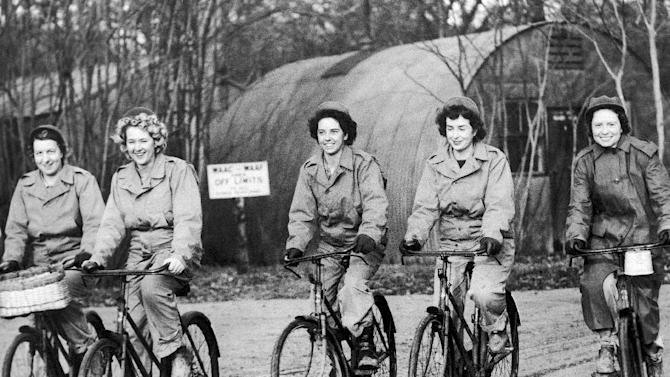 FILE - In this Dec. 22, 1943, file photo, members of the Women Army Corps (WAC) stationed at a U.S. medium bomber station in England, ride bicycles on their way to work. (AP Photo, File)