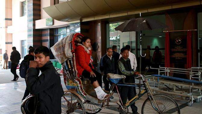 Injured woman waits in a rickshaw for a wheelchair at a trauma centre, in the aftermath of Saturday's earthquake, in Kathmandu, Nepal