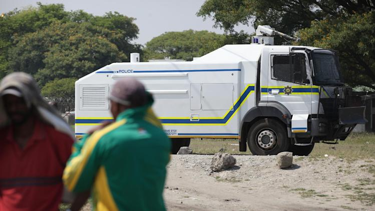 A police truck passes by a meeting of striking miners near Rustenburg, South Africa, on Wednesday, Nov. 14, 2012. Workers discussed a possible deal with Anglo American Platinum, or Amplats, on Wednesday as their weeks-long strike continued. Amplats is the world's top producer of platinum. (AP Photo/Jon Gambrell)