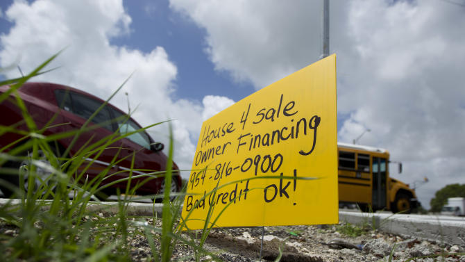 In a Wednesday, May 2, 2012 photo, a house for sale sign stands beside a Hollywood, Fla. street as cars drive past. The cheap signs smashed into lawns and along the corners of busy intersections have vexed Hollywood Mayor Peter Bober for the past few years.   He now uses a software program that makes robocalls to the businesses, sometimes about 20 a day, to discourage posting the signs. The idea has been so successful they've seen a 90 percent reduction of signs in some areas and cities as far away as Canada are calling about the program.(AP Photo/J Pat Carter)