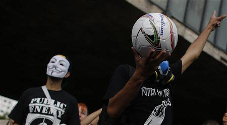 A man holds a soccer ball during a protest against the 2014 World Cup, in Sao Paulo