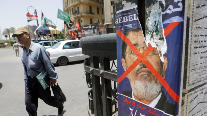"An Egyptian walks by a poster of Tamarod, Arabic for ""rebel"", a campaign calling for the ouster of Egyptian President Mohammed Morsi and for early presidential elections, in Cairo, Egypt, Friday, June 7, 2013. Young activists are trying to rally public discontent with Egypt's Islamist President Mohammed Morsi by fanning out in the streets and collecting millions of signatures on a petition calling for his removal. Morsi's Muslim Brotherhood has dismissed the campaign as irrelevant, even illegal, but the signature drive has stirred up Egypt's politics as the president nears the end of his tumultuous first year in office. Arabic at the bottom of the poster reads,""Down with Muslim Brotherhood rule, June 30, at the presidential palace."" (AP Photo/ Amr Nabil)"