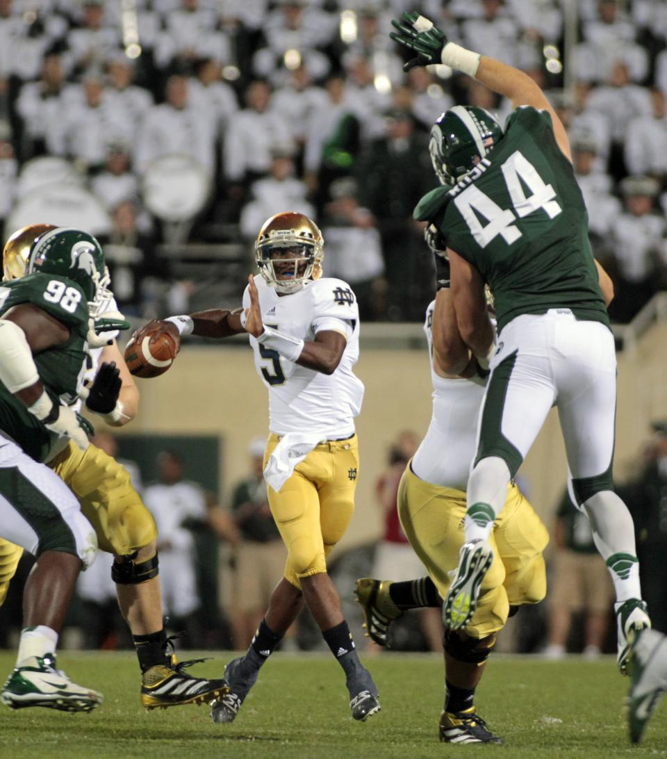 Notre Dame quarterback Everett Golson, center, looks to pass between Michigan State's Marcus Rush (44) and Anthony Rashad White (98) during the first quarter of an NCAA college football game, Saturday, Sept. 15, 2012, in East Lansing, Mich. (AP Photo/Al Goldis)