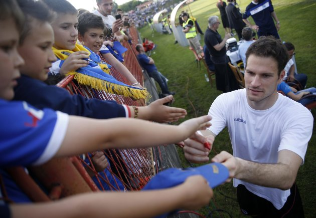 Bosnia's national soccer team goalkeeper Asmir Begovic signs autographs after a humanitarian match against the Bosnia U21 team in Gradacac, May 22, 20...