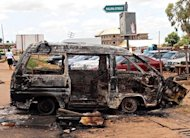 A woman walks near a minibus burnt by an angry mob in reaction to suicide bomb attacks on the Shallom Church of God during church service on Sunday in the Trikania neighbourhood in Kaduna. Fresh explosions and gunfire rocked a northeastern Nigerian city on Monday, a day after suicide attacks claimed by Islamists and reprisal violence by rampaging Christian mobs left 52 people dead