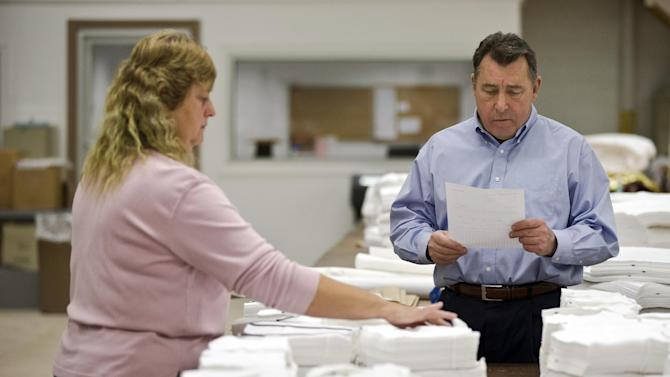 In this Monday, Oct. 15, 2012 photo, Gloria Bambrick counts and stacks components of T-shirts as CEO Walter Meck reviews an order at FesslerUSA apparel manufacture in Orwigsburg, Pa. Family-owned FesslerUSA has survived war and depression, free trade and foreign imports to produce millions of knitted garments from its base in eastern Pennsylvania. Production will shut down in early November, tossing 130 employees out of work and ending a run of nearly 113 years. Meck blames the historic mill's demise on weak consumer spending, fresh competition from Asia, tighter credit standards that he says prevented the company from getting a loan, and a lack of interest from private investors and potential buyers. (AP Photo/Matt Rourke)