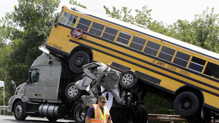 FILE - In this Aug. 5, 2010 file photo, a rescue worker is seen at the scene of an accident involving two school buses, a tractor-trailer and another passenger vehicle, near Gray Summit, Mo. Federal safety investigators say a 19-year-old driver was texting at the time his pickup truck, two school buses and other vehicles collided in a deadly pileup on an interstate highway in Missouri last year. The National Transportation Safety Board (NTSB) released the information Monday. The board is scheduled to meet Tuesday to hear the results of an investigation into the accident near Gray Summit, Mo., and to make safety recommendations.  (AP Photo/Jeff Roberson, File)