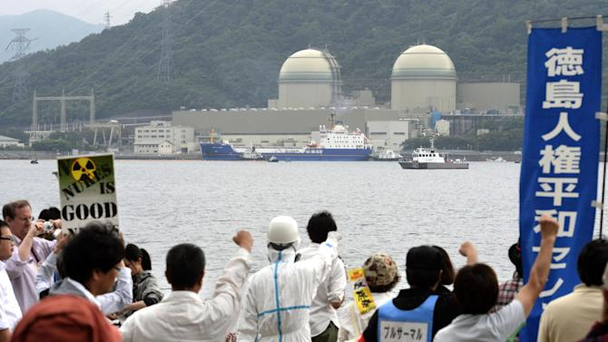 Protesters punch the air as a freighter, center in background, carrying MOX, a mixture of uranium and plutonium oxide, arrives at the Takahama nuclear power station, background, in Takahama town, Fukui prefecture, Japan, Thursday, June 27, 2013. The power plant on the Sea of Japan coast has received the first shipment of reprocessed nuclear reactor fuel sent from France since the 2011 disaster that forced it to shut down reactors. Operators of the plant are hoping to use the fuel once they get the go-ahead to restart their reactors. (AP Photo/Kyodo News) JAPAN OUT, MANDATORY CREDIT