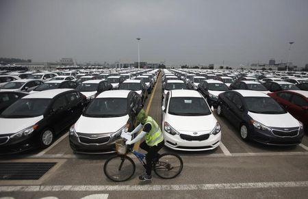 A worker cycles past cars made by Hyundai and Kia at the company's shipping yard in Pyeongtaek