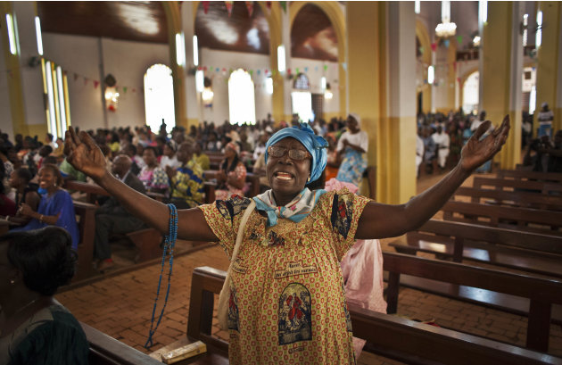 A churchgoer raises her hands as she sings in the New Year's Day morning mass at the Notre Dame Cathedral of the Immaculate Conception in Bangui, Central African Republic, Tuesday, Jan. 1, 2013. Presi