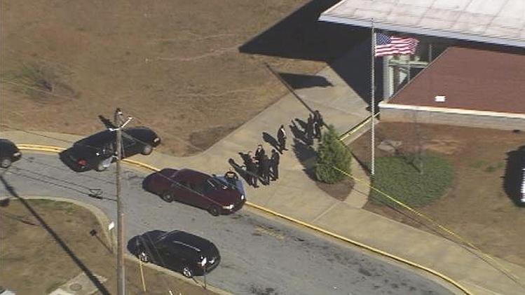 "In this image made from video and released by WSB-TV, authorities investigate the scene of a school shooting, Thursday, Jan 31, 2013 in Atlanta. Authorities say a 14-year-old has been wounded in a shooting at an Atlanta middle school and a suspect has been taken into custody. Atlanta police spokesman Carlos Campos says the wounded student has been taken ""alert, conscious and breathing"" to Grady Hospital. (AP Photo/WSB-TV)"