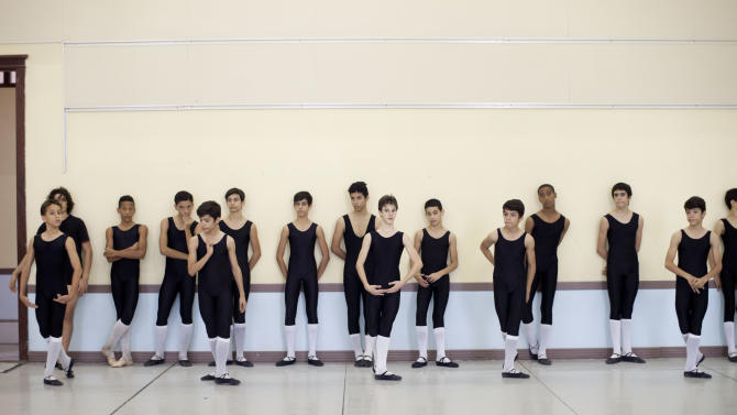 CORRECTING MARCO TO MARCOS -  In this April 3, 2013 photo, identical triplets Marcos, Cesar and Angel Ramirez Castellanos stand in the front row during their ballet class at the National School of Ballet in Havana, Cuba. The 13-year-olds have already separated themselves from their peers technically and artistically, and all three have the talent to make a big splash in the ballet world when they grow up. (AP Photo/Ramon Espinosa)