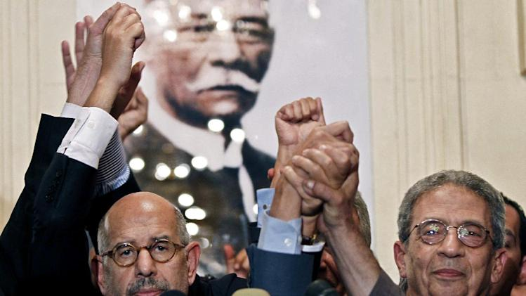 FILE - In this Thursday, Nov. 22, 2012 file photo, former director of the U.N.'s nuclear agency and Nobel peace laureate, Mohamed El Baradei, left, and former Egyptian Foreign Minister and presidential candidate, Amr Moussa, raise their hands in solidarity after addressing a news conference flanked by other prominent politicians, not shown, from outside the Muslim Brotherhood, to decry what was interpreted as a de facto declaration of emergency law by Egyptian President Mohammed Morsi, in Cairo Egypt. An Egyptian official says the country's top prosecutor has ordered an investigation into accusations against opposition leaders, Mohammed ElBaradei, Amr Moussa, and Hamdeen Sabahi, of incitement to overthrow the regime. A photo of Saad Zaghloul, an Egyptian revolutionary, and statesman whose exile by Britain caused disturbances in Egypt, ultimately leading to the Egyptian Revolution of 1919. (AP Photo/Mostafa El Shemy, File)