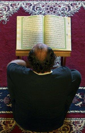 A Lebanese man reads a Quran, the Muslim holy book,…