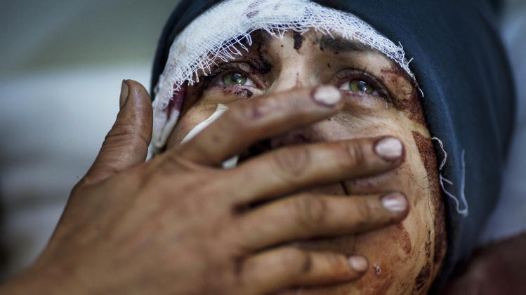FILE - Aida cries as she recovers from severe injuries after the Syrian Army shelled her house in Idlib, north Syria, Saturday, March 10, 2012. Aida's husband and two of her children were killed after their home was shelled. (AP Photo/Rodrigo Abd, File)