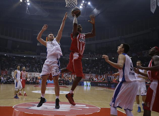 Olympiakos' Bryant Dunston scores as Anadolou Efes' Dusko Savanovic, 20, tries to stop him during their Euroleague basketball match of Top 16 in the port of Piraeus, near Athens, Thursday, Feb