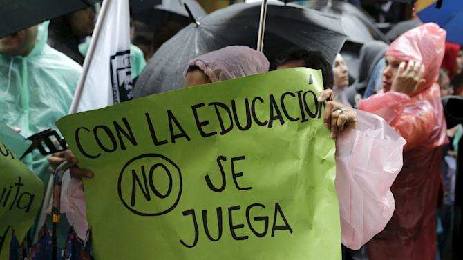 Paraguayan students from private and public schools protest under the rain in front of the Ministry of Education's building in Asuncion