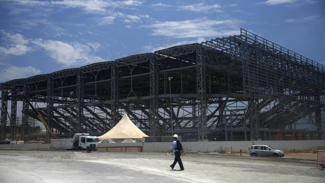 Visitor walks in front of the construction site of the Rio 2016 Olympic Park during a media briefing in Rio de Janeiro