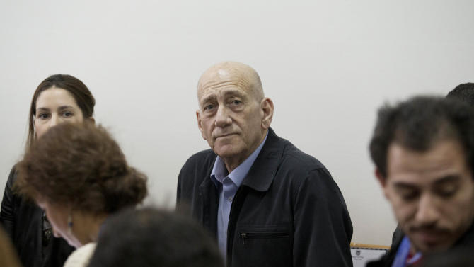 Former Israeli Prime Minister Ehud Olmert, center, waits for a verdict in Jerusalem's District Court on Monday, March 30, 2015. The court later found Olmert guilty of accepting bribes in a retrial of corruption charges. (AP Photo/Abir Sultan, Pool)
