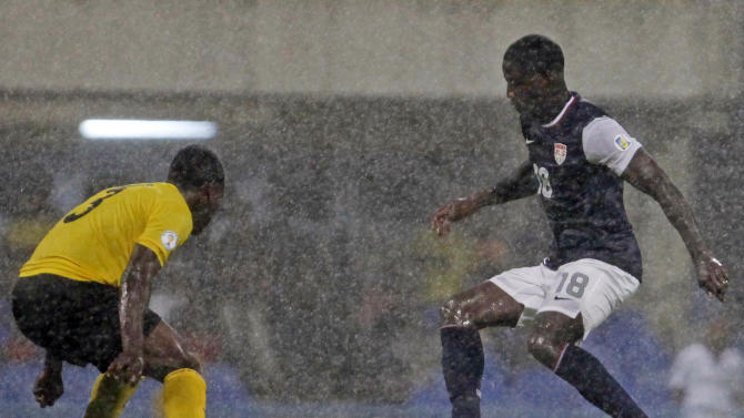 Under pouring rain, US' Eddie Johnson, right, challenges Antigua and Barbuda's Zaine Sebastian Francis-Angol during a 2014 World Cup qualifying soccer match in St. John, Antigua and Barbuda, Friday, Oct. 12, 2012. (AP Photo/Ricardo Arduengo)