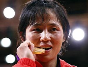 North Korea's An Kum Ae bites her gold medal as she celebrates during the awards ceremony for women's -52kg judo competition at London 2012 Olympic Games