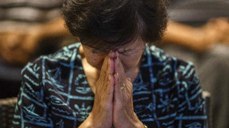 Woman prays during a special prayer held for the victims of downed Malaysia Airlines Flight MH17 in Kuala Lumpur
