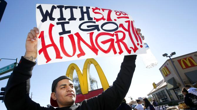 Alex Robles joins dozens of sign-holding protesters at a rally against low wages for fast-food workers, in front of a McDonald's Thursday, Dec. 5, 2013, in Phoenix. (AP Photo/Ross D. Franklin)