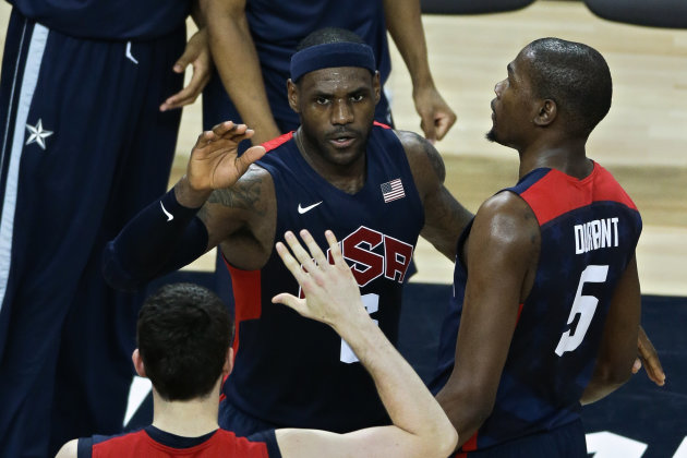 United States' Lebron James, center, is congratulated by teammates Kevin Durant, right, and Kevin Love, bottom, after slamming a dunk in a men's basketball semifinal game against Argentina at the 2012
